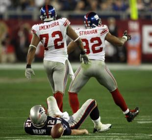 Michael Strahan (R) and Osi Umenyiora (L) of the New York Giants celebrate after sacking quarterback New England Patriots Tom Brady (on ground) during Super Bowl XLII at the University of Phoenix Stadium in Glendale, Arizona, 03 February 2008. AFP PHOTO/Timothy A. CLARY (Photo credit should read TIMOTHY A. CLARY/AFP/Getty Images)